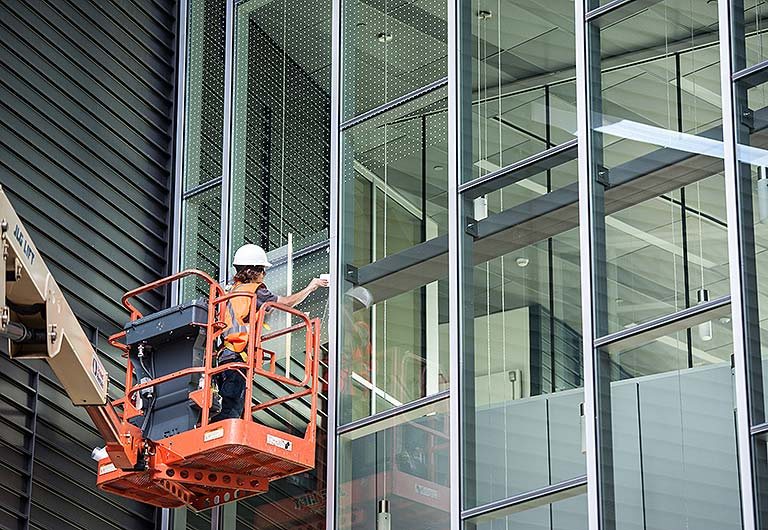 An image of a worker applying window patterns at the ESIF.