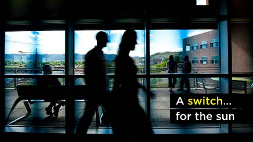 A photo of two people walking by a window at NREL.