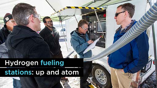 A photo of five men at a hydrogen fueling station trailer.