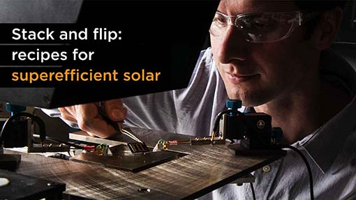 A photo of an NREL scientist looking closely at a solar cell.