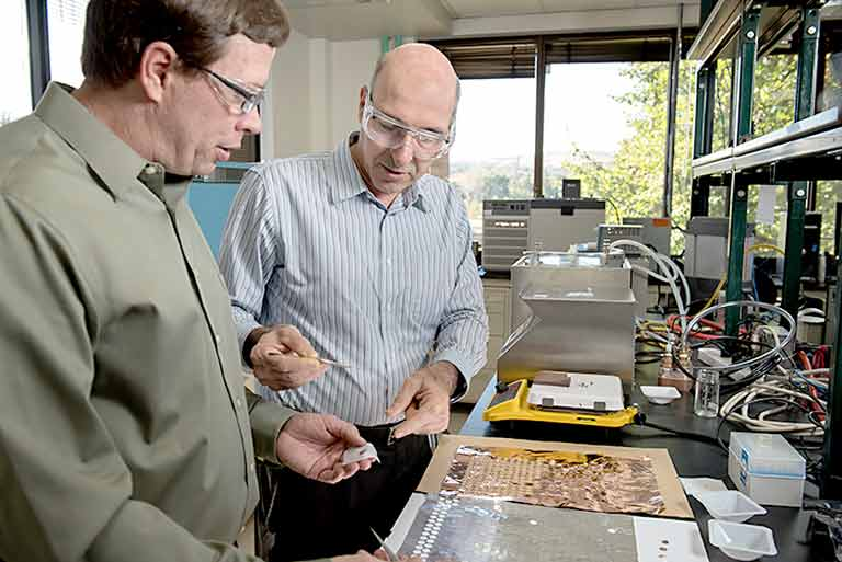NREL researchers, Matthew Keyser and Ahmad Pesaran with the battery internal short-circuit device in the lab.