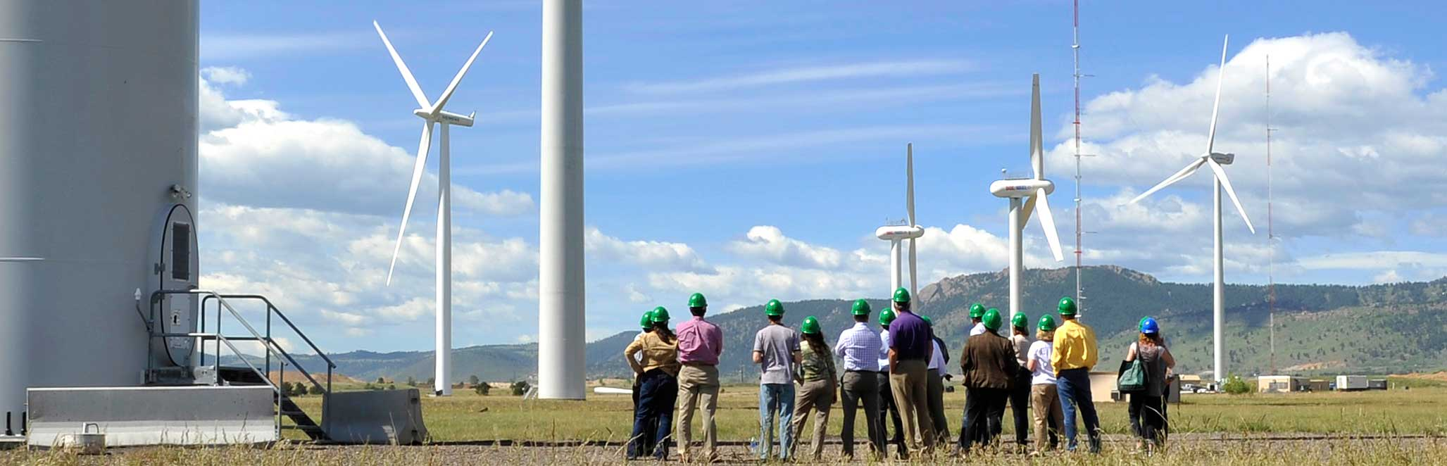 A group of NREL Energy Execs gather around the bottom of a wind turbine with blue skies and fields in the foreground.