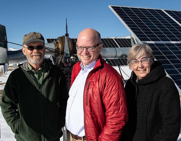Photo of three people standing in front of a PV array
