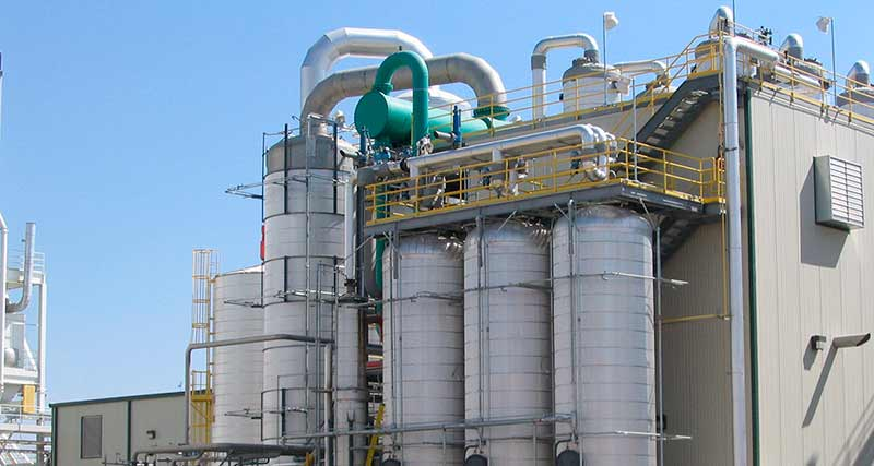 Large biorefinery including four vertical columns, piping, and metering equipment