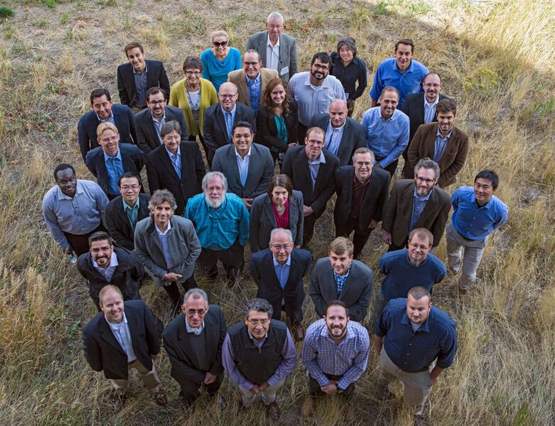 Photograph of NARIS project team members from government and industry in the United States, Canada, and Mexico. Members are posed outdoors and looking up at the camera. Photo taken at NREL during NARIS kickoff meeting.