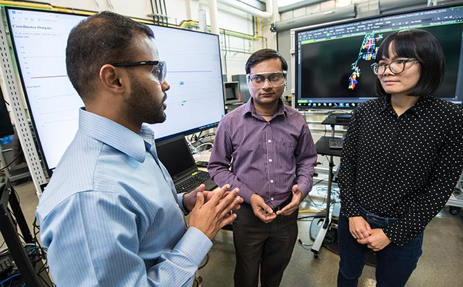 NREL researchers work on NREL's advanced distribution management system test bed.