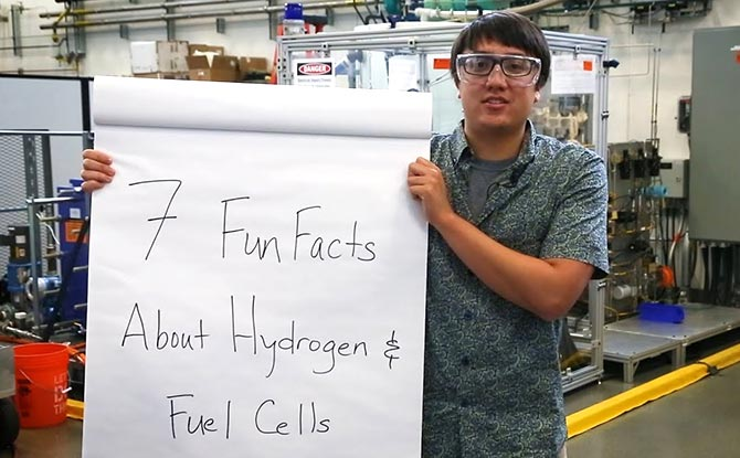 "An employees hold a sign that says ""7 Fun Facts About Hydrogen"""