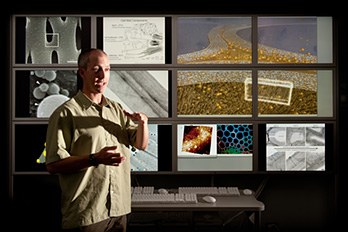 Photo of a man in front of multiple computer screens  that present different views of ultra structures of pretreated biomass materials in NRELs Cellular