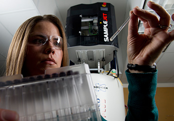 Photo of a woman wearing safety glasses in a laboratory looking at pipette samples and holding box of test tubes