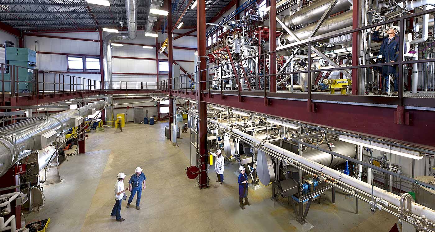 Interior of industrial, two-story building with high-bay, piping, and large processing equipment. Three workers in hard hats.
