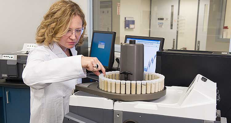 woman in lab looking at turn table of samples