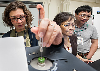 Photo of two women and one man in a laboratory measuring hydrogen production of engineered microbes in a gas chromatograph.