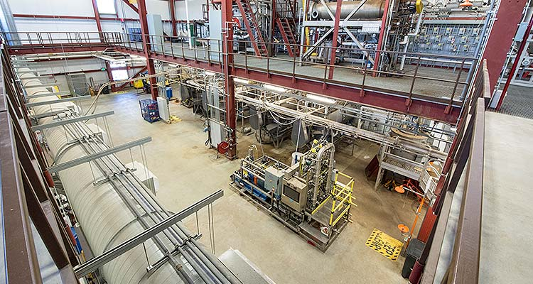 Photo of a large, industrial space with two floors of testing equipment.