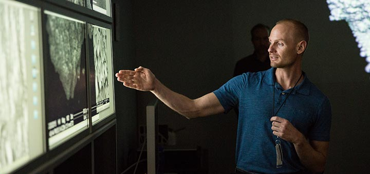 Man pointing to a series of large computer monitors showing molecular images.