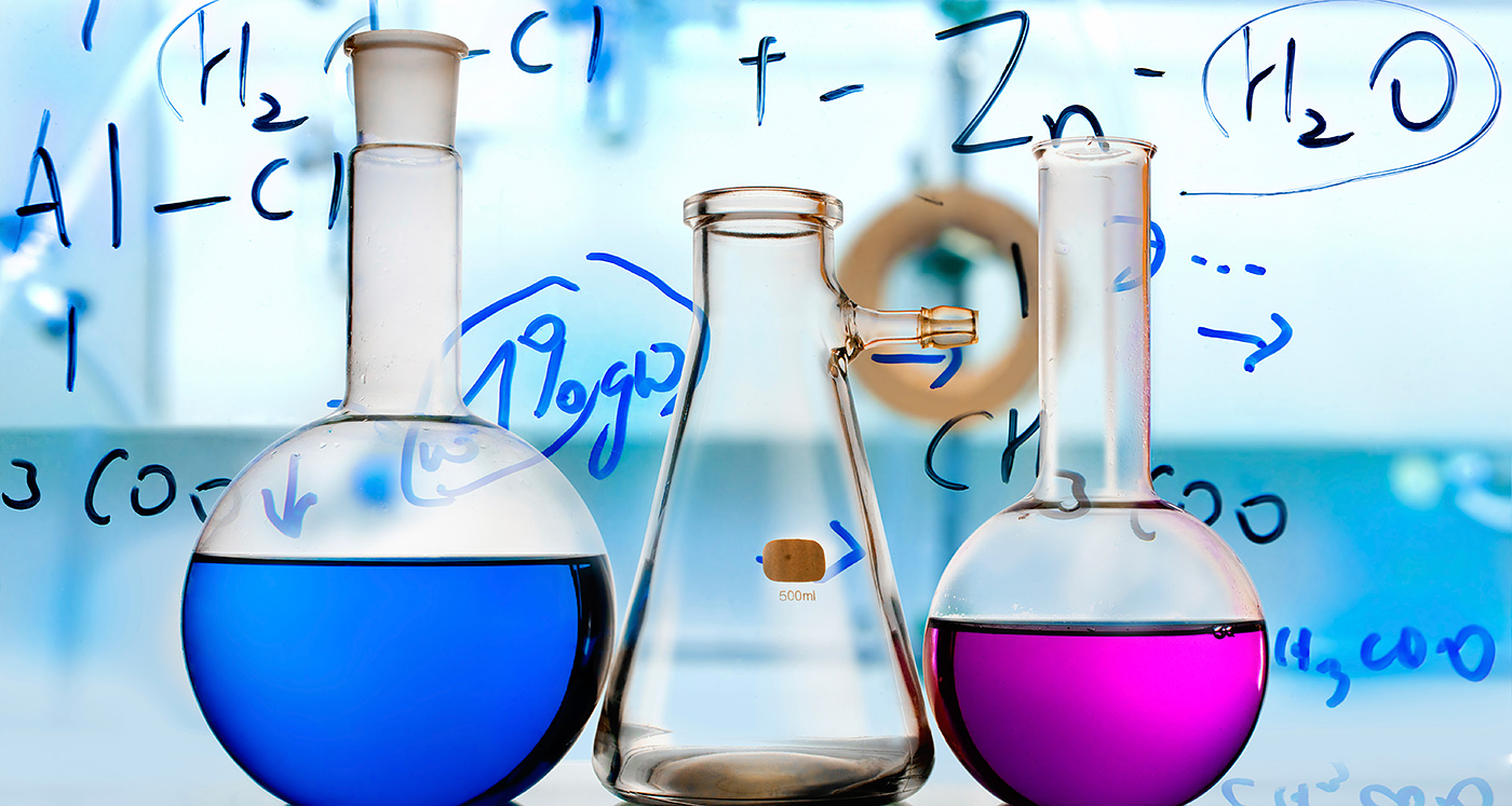 Photo of three pieces of laboratory glassware; one contains a blue liquid and one is half filled with pink liquid; chemical formulas are handwritten and superimposed on top of the image.