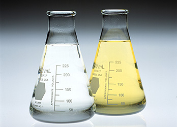 Photo of two Erlenmeyer flasks showing a comparison between a clean Fischer-Tropsch diesel fuel (left flask with clear liquid) and conventional No. 2 diesel fuel (right flask with pale yellow liquid).
