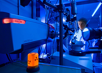 Photo of a researcher in a blue-lit laboratory using an x-ray crystallography instrument to image crystal diffraction patterns of protein for 3-D imaging of enzymes.