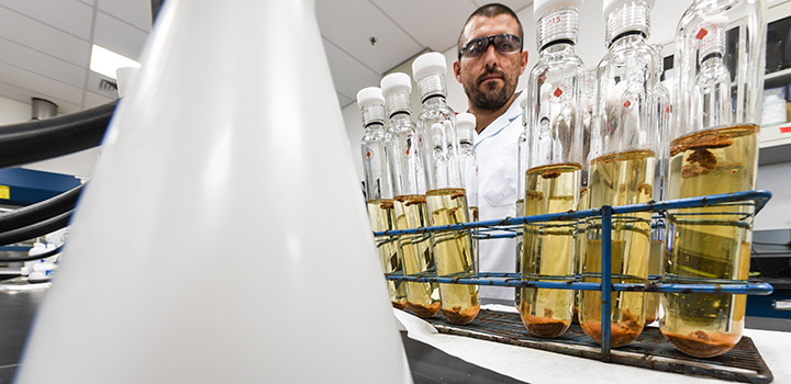 A man in safety glasses and lab coat stands behind a row of glass vials with yellow liquid in a laboratory.