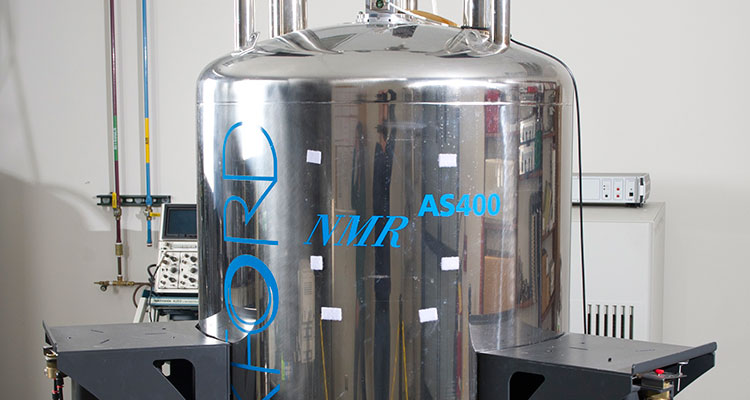 Photo of a 400 MHz Agilent Unity Inova NMR Spectrometer, which is composed of a large metal tank on a three-legged metal stand; clear plastic tubes and wires stick out of the top and bottom of the tank.