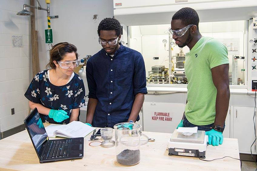 Researchers and JUMP into STEM intern examine graphite pucks in an ESIF lab.