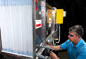 Photo of an engineer working on a first generation prototype desiccant-enhanced evaporative air conditioner that links to a fact sheet about NREL's Energy-Saving Technology for Air Conditioning Cuts Peak Power Loads Without Using Harmful Refrigerants.