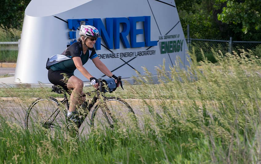 A woman riding her bike past the NREL entrance sign.