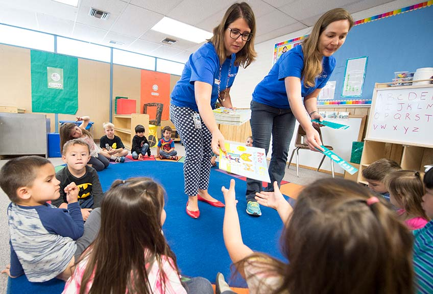 Two female NREL staff members hand out books to children in a classroom.