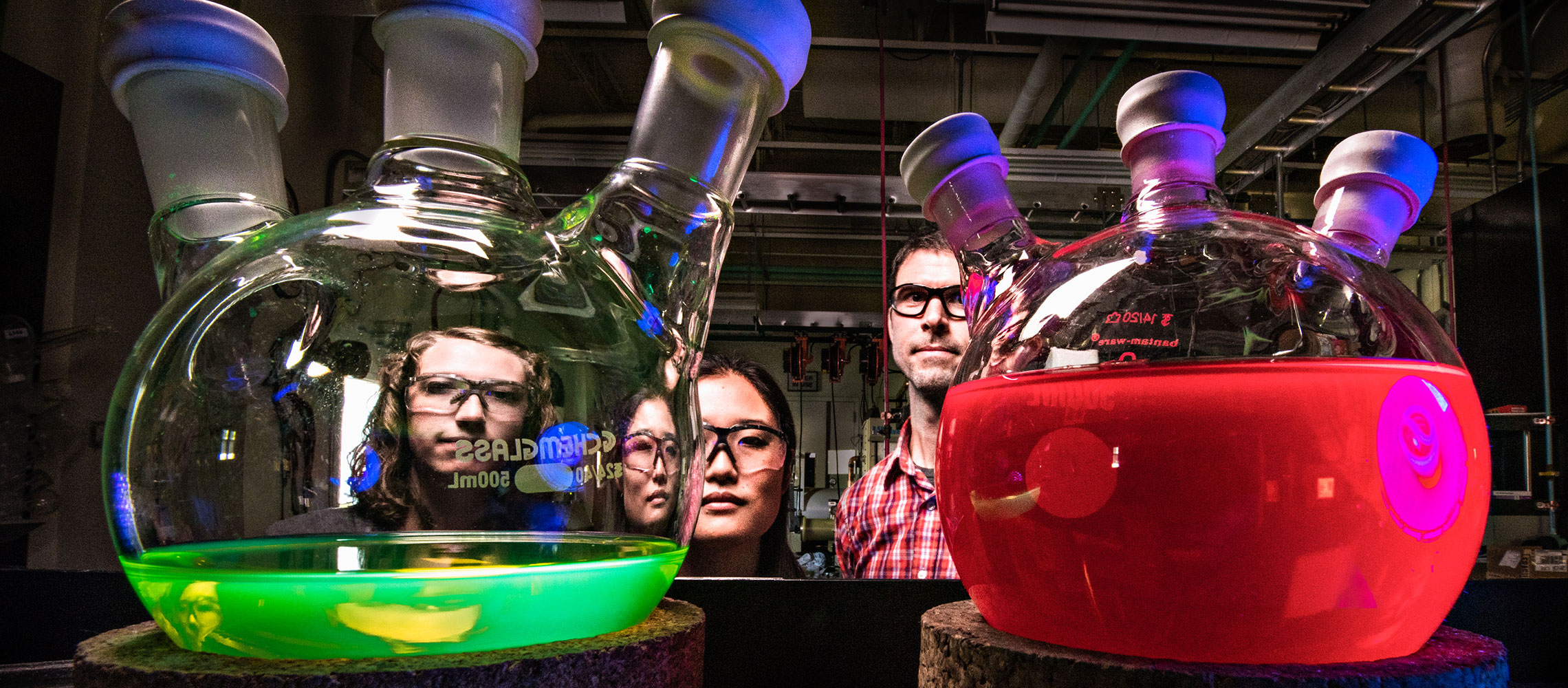 Photo of two laboratory beakers with a male and two females standing behind them.