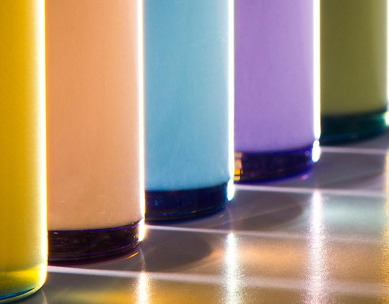 Photo of five glass tubes filled with colored fluids, from yellow, to orange, to blue, to violet, to green.