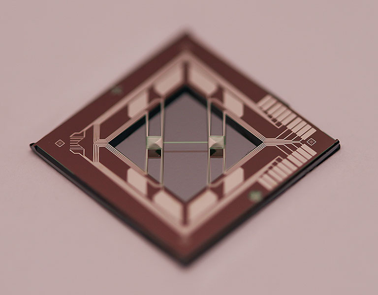 Photo of brown diamond-shaped structure with various light-colored circuit-like components along the edges. Two wire-like objects span the center distance across the edges.