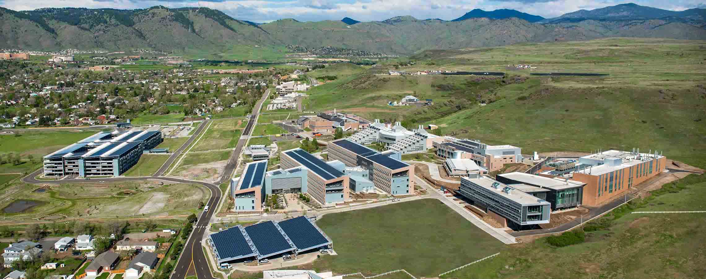 Photo of an aerial view of the NREL South Table Mesa campus buildings with mountains in the background.