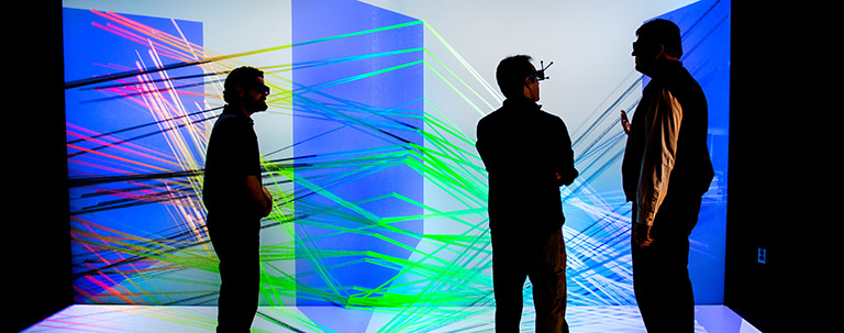 Photo of three people viewing a large-scale 3D visualization