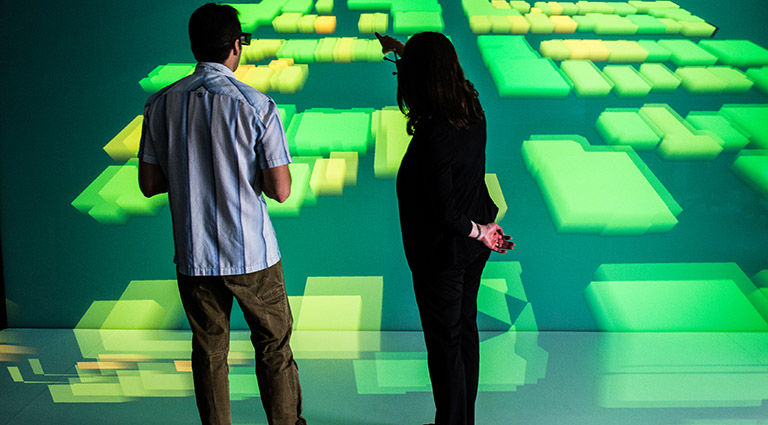 Photo of two researchers standing in front of a large-scale 3D visualization of a community energy grid model