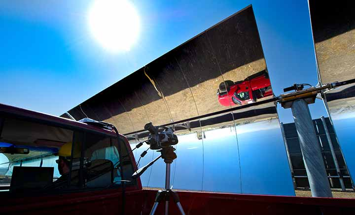 A red truck is reflected upside-down in a parabolic trough on a sunny clear day.