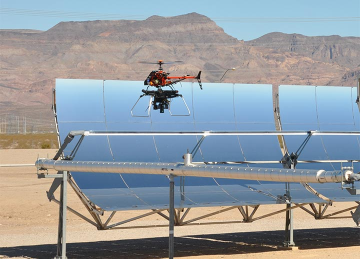 A small helicopter drone hovers near the top of a parabolic trough in the desert in front of mountains.