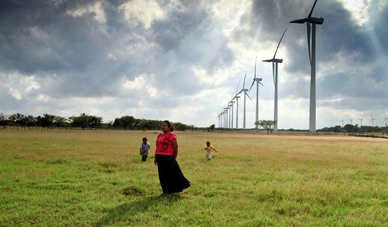 Photo of a Mexican woman and two children in a field with large wind turbines behind them.
