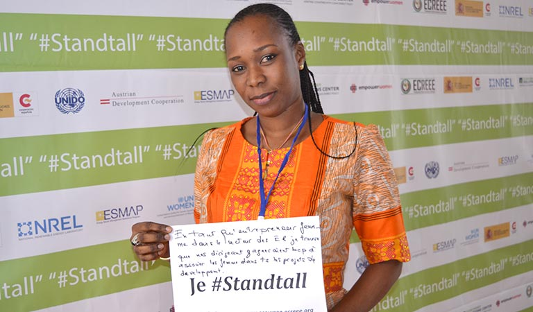 "Photo of a black woman in an orange dress holding a piece of white paper that says: ""Je #Standtall"""