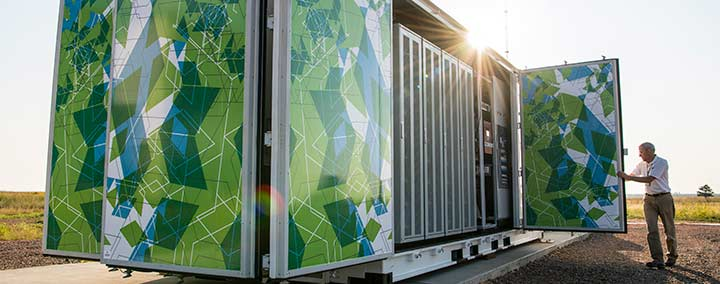 Photo of a man closing the door of a large, multicolored metal box that is roughly the size of a semi-truck trailer. Inside the box are batteries that make up a 1-megawatt battery energy storage system.