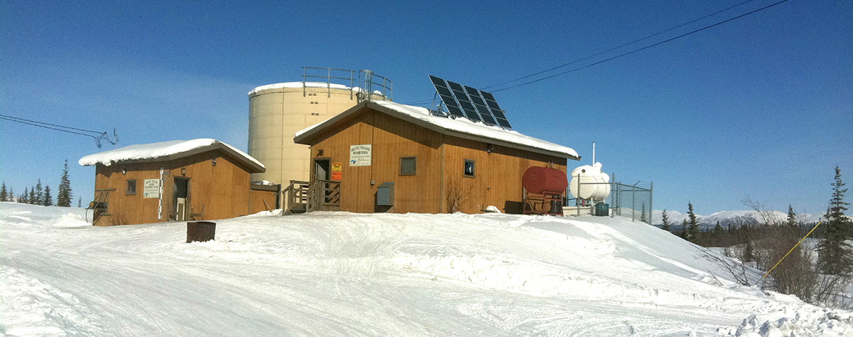 A washeteria in Alaska with solar panels on the roof and a propane tank and water tank next to the building.