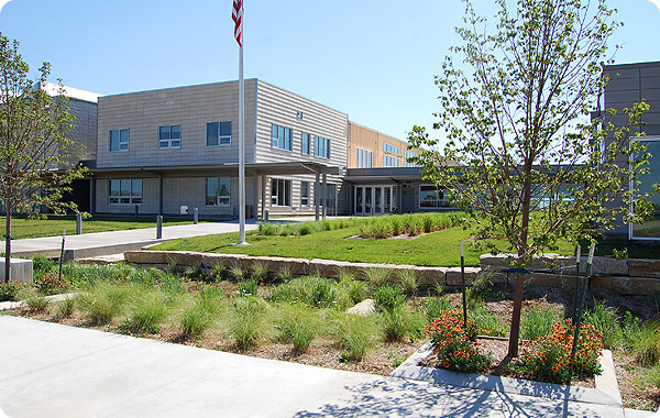 Photo of a new school building behind a flag pole and trees.