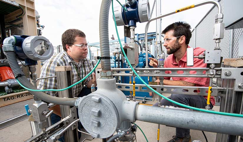 Photo of two researchers working on equipment at the hydrogen storage pad at the Energy Systems Integration Facility.