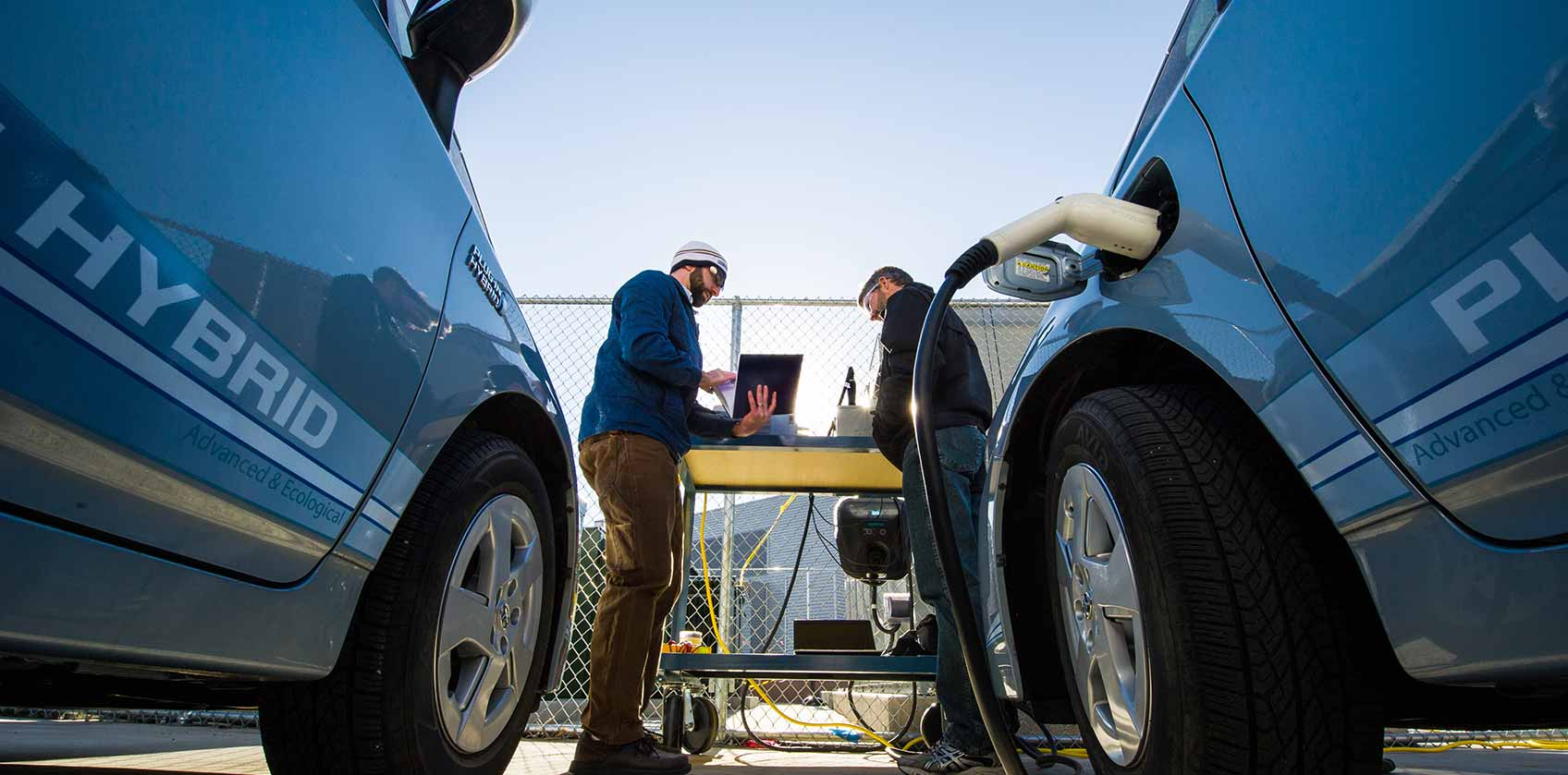 Photo of two men working on testing electric vehicle technologies