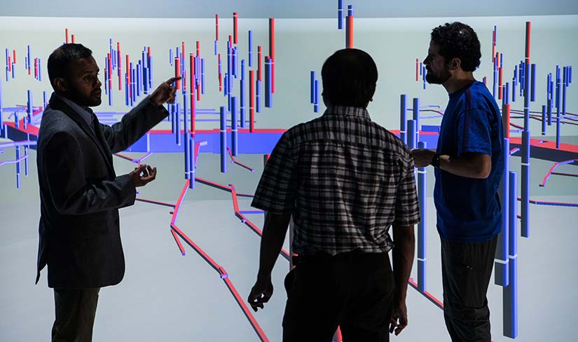 Photo of three researchers looking at a 3D visualization of data on a large screen at the Insight Center Visualization Laboratory in the ESIF.