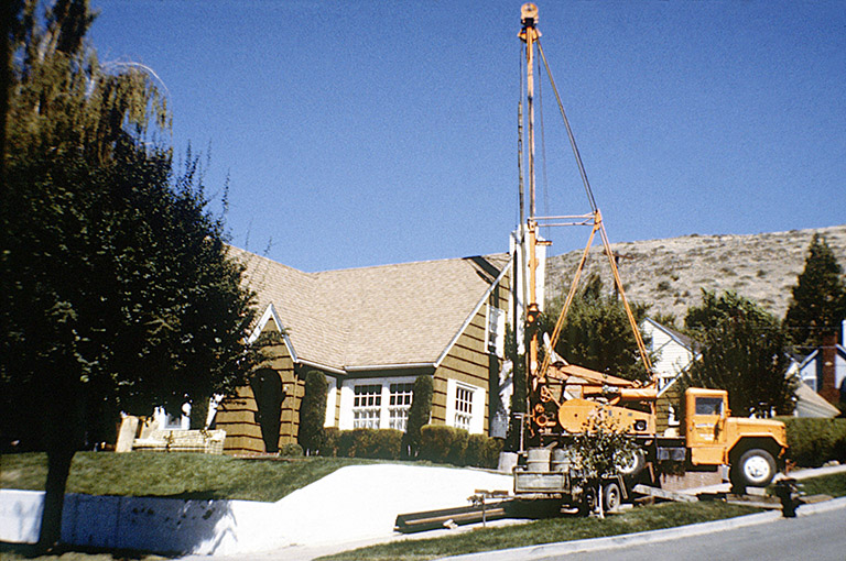 Photo of a geothermal well drill with cable rig installing a residential heat exchanger.