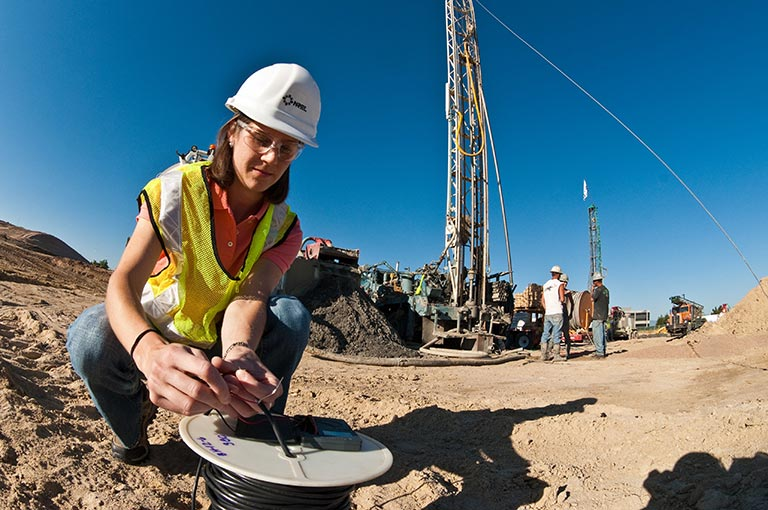 Photo of NREL researcher with a hard hat on winding wire onto a coil at a geothermal drilling site.