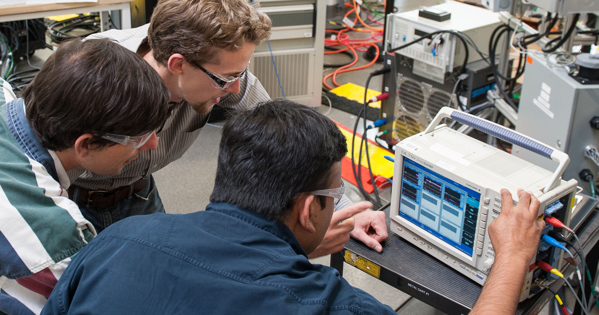 Photo of three researchers working with inverter hardware in a lab.