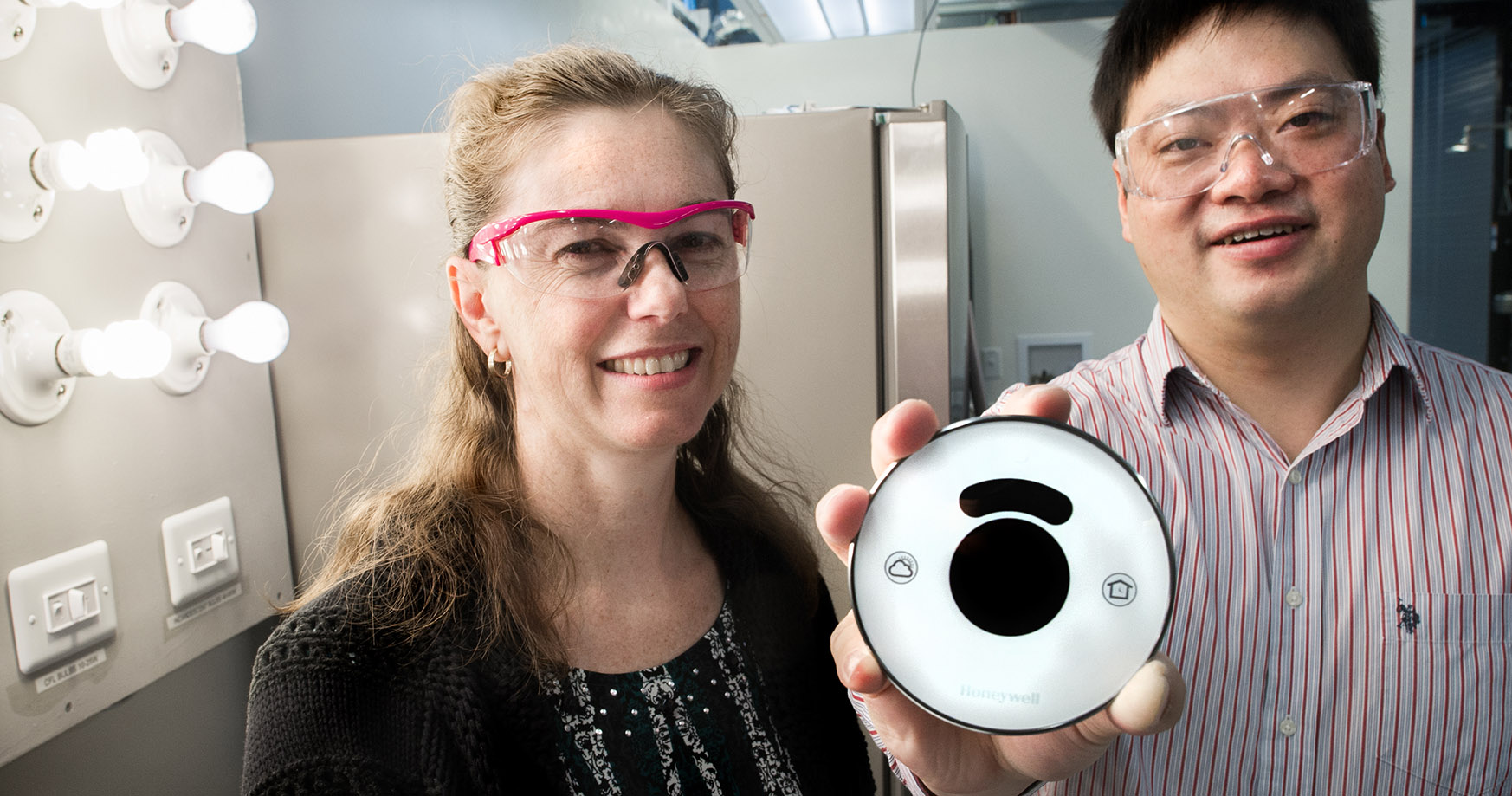 Photo of a pair of NREL researchers who received a record of invention for a home energy management system in a smart home laboratory.