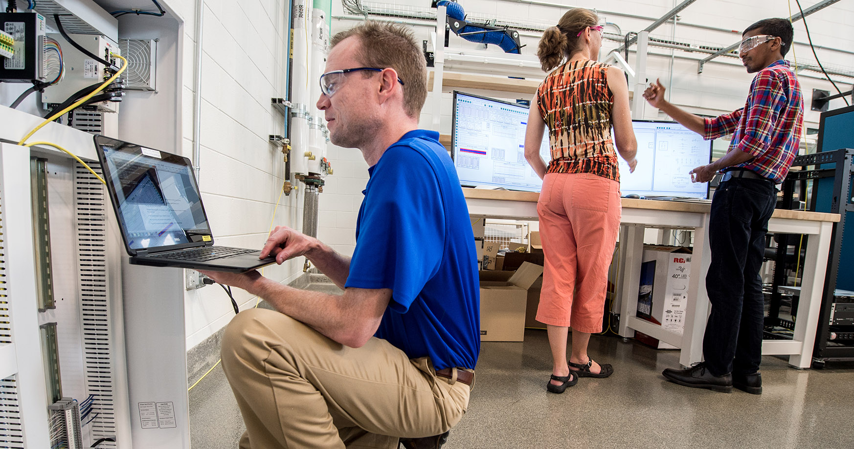 NREL researchers work on controller- and power hardware-in-the-loop test setups to evaluate the performance of microgrid controllers.
