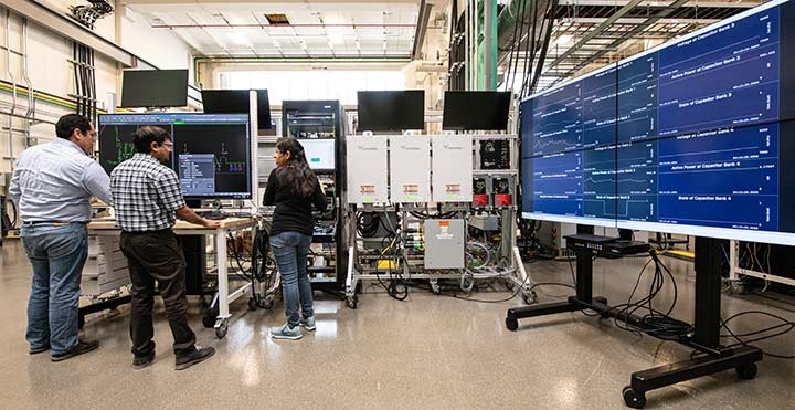 NREL researchers work on the ADMS Test Bed in the Power Systems Integration Lab in the ESIF.