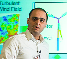 A photo of a man in a white shite with a colorful PowerPoint presentation in the background.